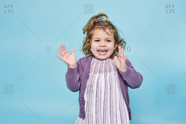 Cheerful small child in purple dress and knitted cardigan smiling at camera and clapping while standing alone against light blue background in modern studio