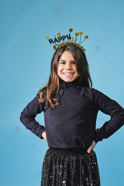Happy preteen in black and gold headgear with wishes happy New Year smiling at camera with hands on hips against light blue background in modern studio
