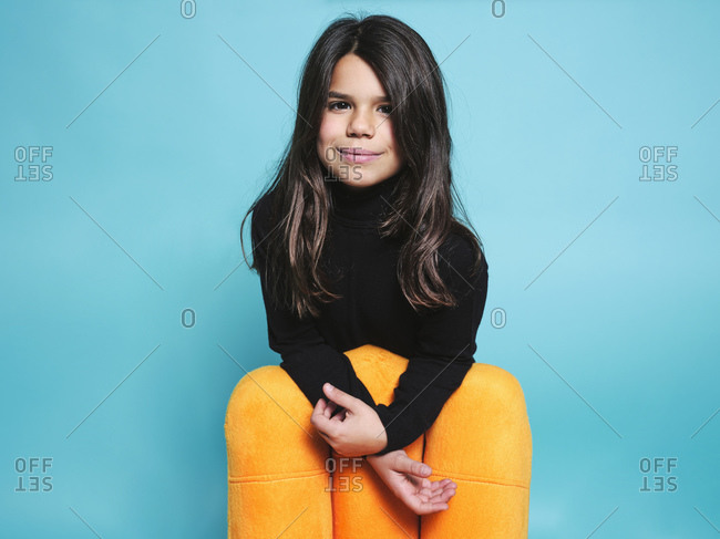 Happy preteen girl in black casual clothes smiling looking at camera while leaning behind yellow armchair against light blue background in contemporary studio
