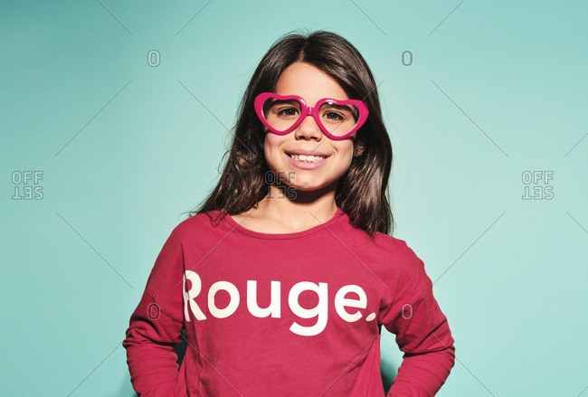 Happy preteen girl in pink heart shape glasses and casual clothes smiling at camera while standing against turquoise background in modern studio