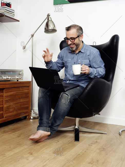 man working on laptop and talking on video conference smiling having relaxed coffee on couch at home