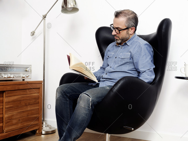 man reading a book having a relaxed coffee in the armchair at home