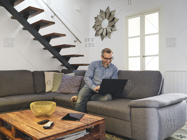 Man working on laptop alone on sofa in living room at home