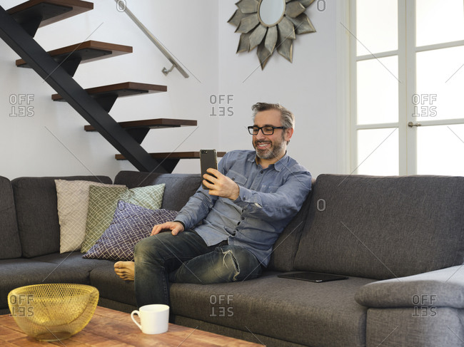 Man talking smiling for a video conference with the phone alone on the sofa in the living room at home