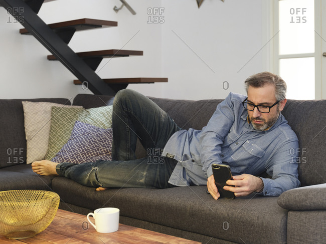 Man using phone alone on sofa in living room at home