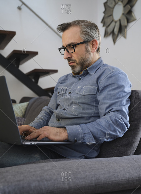 Serious Man using laptop surfing the internet alone on the couch in the living room at home