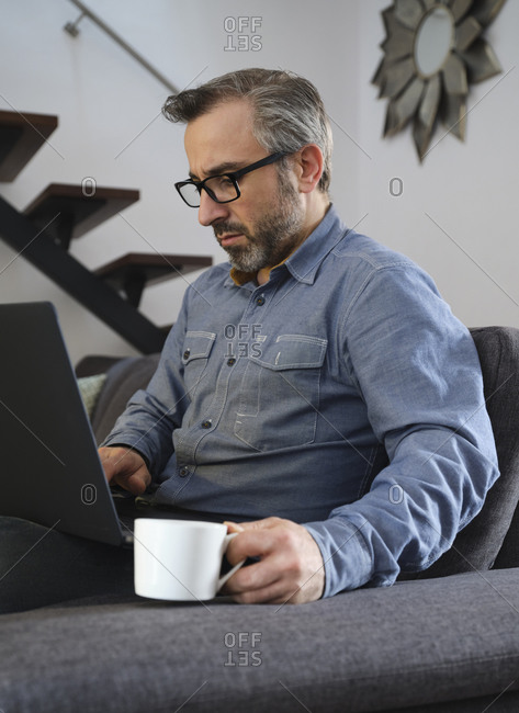 Serious Man using laptop surfing the internet alone on the couch in the living room at home with coffee