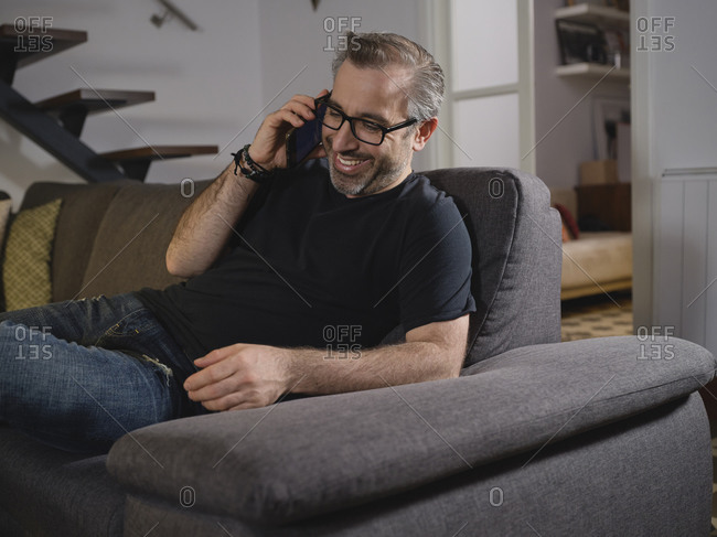 Relaxed man talking on the phone smiling alone on the sofa in the living room at home