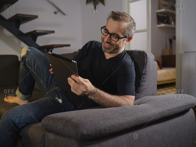 Relaxed man talking on the tablet serious alone on the sofa in the living room at home