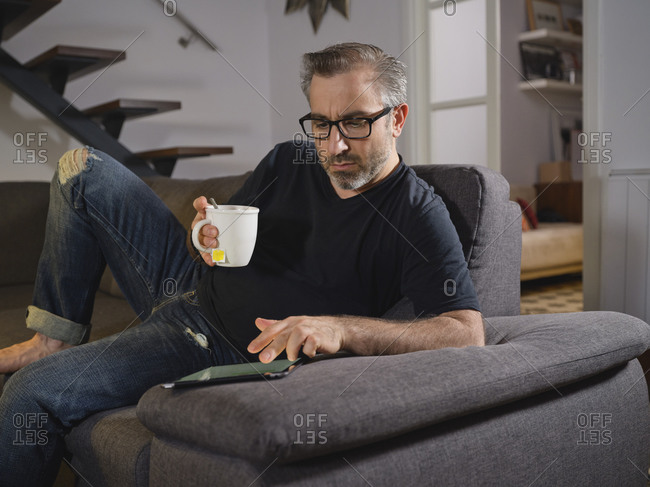 Relaxed man surfing the internet having a tea alone on the sofa in the living room at home
