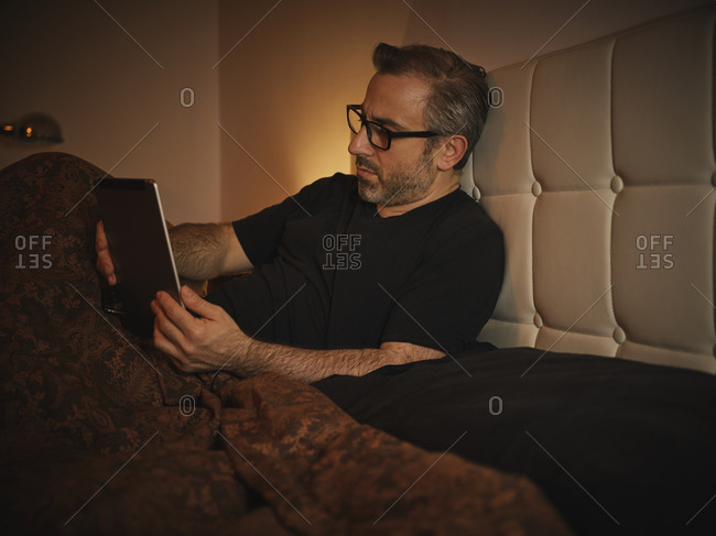 Relaxed and serious man in bed reading on the internet with a tablet before sleeping and resting