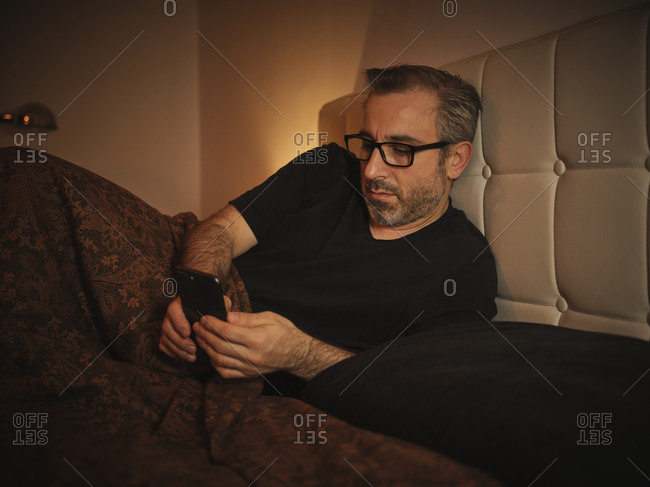 Relaxed and serious man in bed reading on the internet with a phone before sleeping and resting