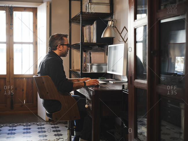 Man working at home desk with computer via internet