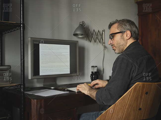 Man working at home desk with computer via internet typing on computer and using mouse