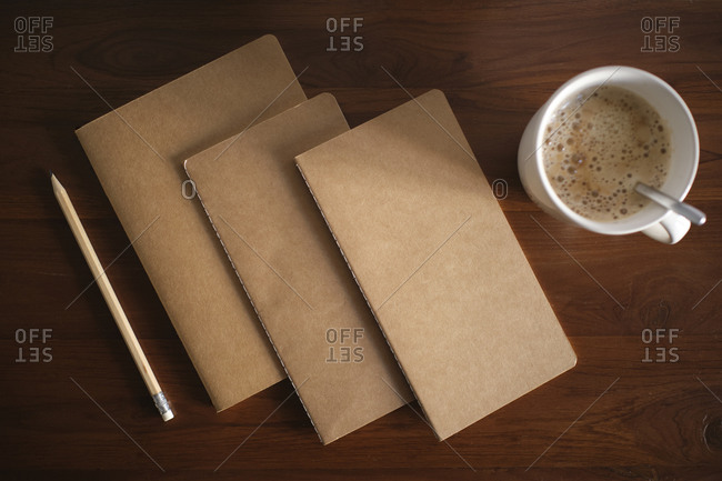 cool traditional notebooks on wooden table and pencil and mug with coffee