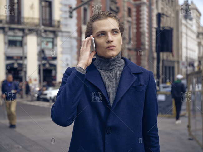 Modern elegant male in trendy coat looking away pensively while having phone conversation on city street