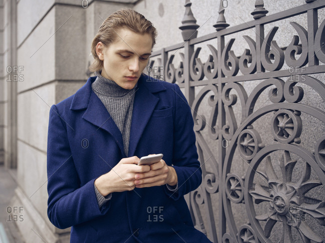 Stylish young man browsing on smartphone on street on city street