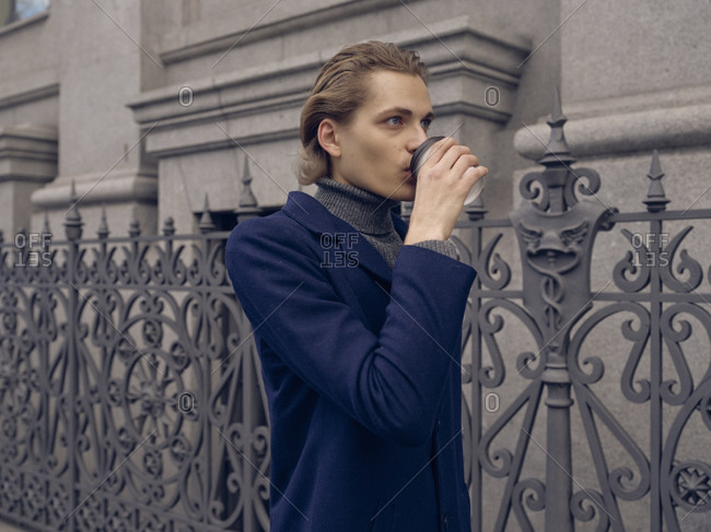 Serious young male with stylish hairdo in trendy coat drinking takeaway coffee while standing near aged metal fence against stone building in city