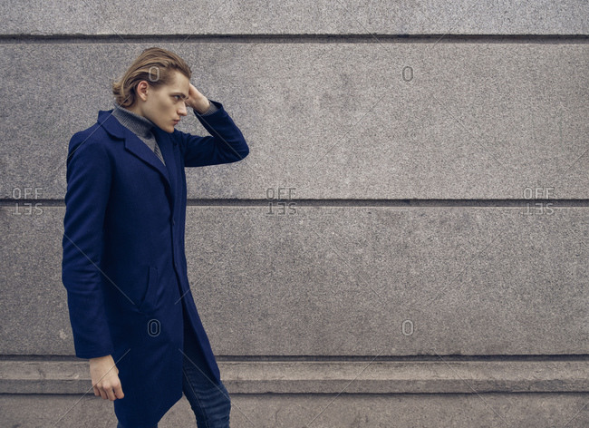 Side view of stylish young male with trendy hairstyle dressed in elegant coat standing against gray stone wall in city