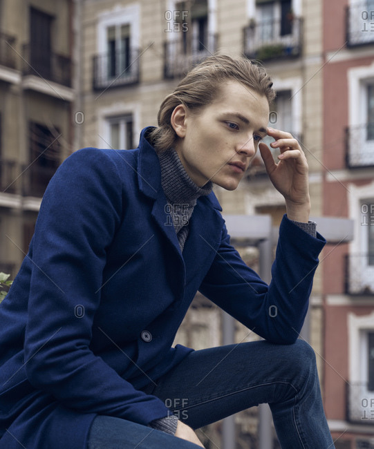 Low angle side view of serious elegant young male in stylish coat leaning on hand and thinking while sitting on street against blurred building