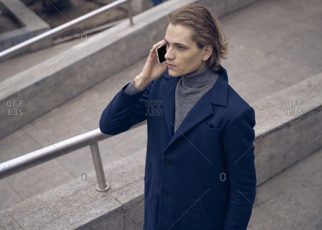 From above of serious young businessman in elegant coat checking message on mobile phone while standing on stone staircase on city street