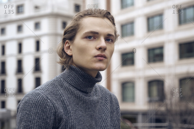 Modern serious young male with stylish haircut in gray warm sweater