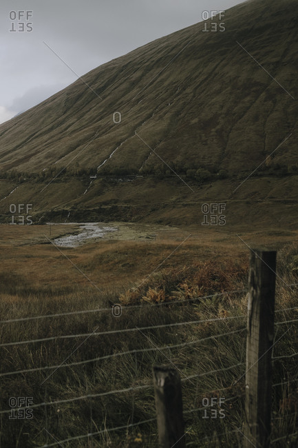 Scottish landscape with wire fence with narrow curvy river flowing among covered with grass hills under cloudy sky in autumn day