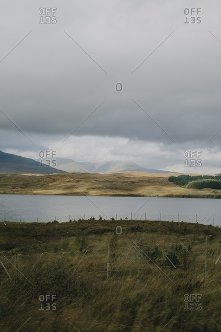 Gloomy Scottish scenery with calm lake under gray cloudy sky in highland in autumn day