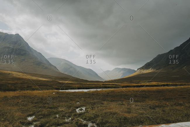 Scottish landscape with narrow curvy river flowing among covered with grass hills under cloudy sky in autumn day