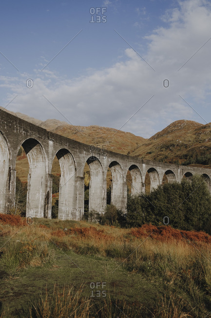 Low angle of old railway viaduct in Scottish highland against mountains and blue cloudy sky in autumn day