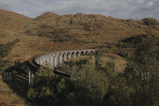 From above old railway viaduct in Scottish highland against mountains and blue cloudy sky in autumn day