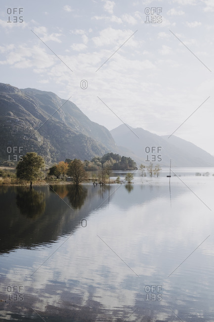 Picturesque scenery of calm lake surrounded by rocky mountains reflected in water in sunny day with cloudy sky in Scotland