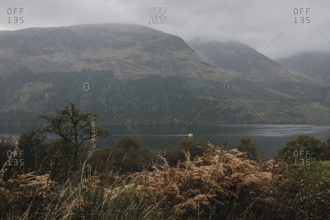 Misty landscape of mountain range covered with fog and clouds near calm lake in Scottish highland
