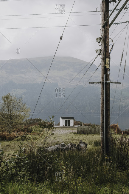 Gloomy Scottish countryside landscape with lonely white house located near mountain lake in overcast day with electric pole and cable in foreground