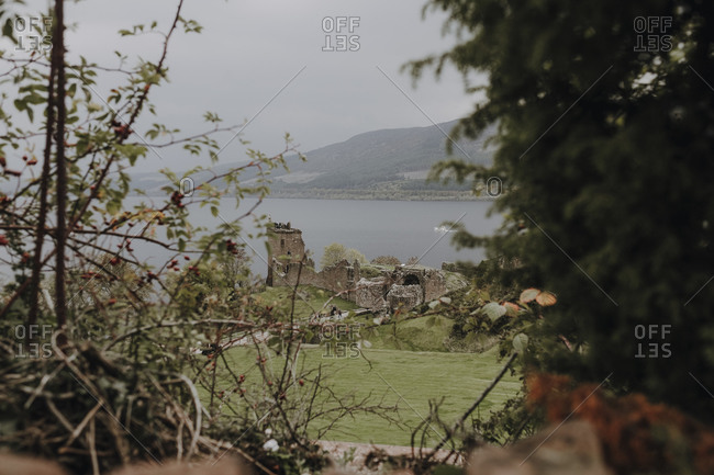 Moody Scottish landscape with ruins of old castle located on shore of lake against foggy hills framed by branches of trees