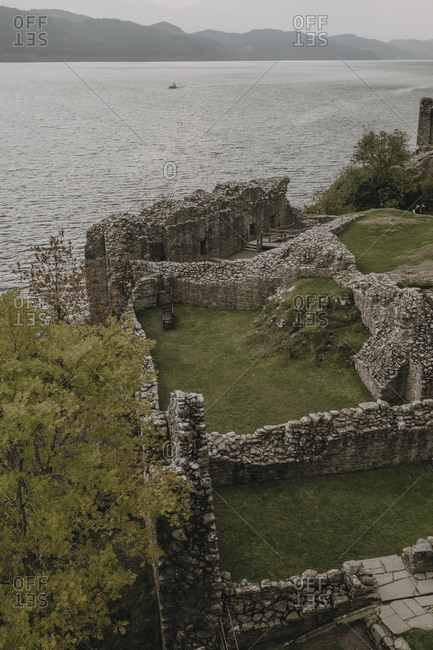 From above of stone walls of ancient castle located on green hill near lake with foggy mountains in background in Scottish countryside