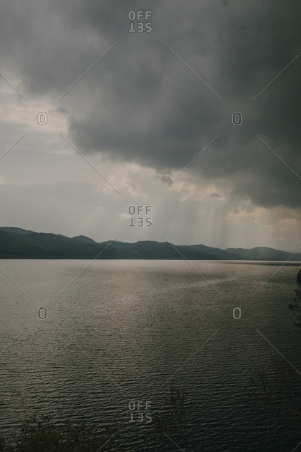 Tranquil landscape with sun rays shining through thick clouds over calm lake with dark water