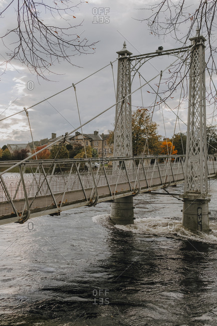 Old suspension bridge crossing river in ancient Scottish city Inverness against gray cloudy sky in autumn day