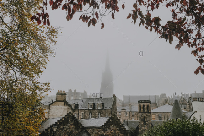 Amazing view of ancient Scottish city Inverness with stone houses and high church building covered with fog framed by branches of colorful autumn trees