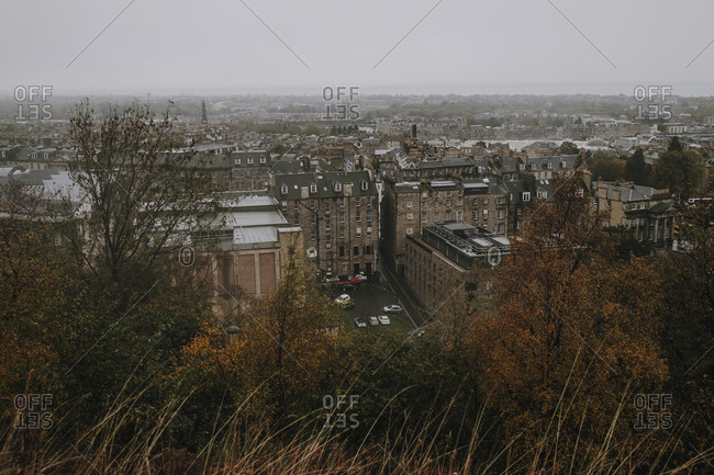 From above cityscape of old city Edinburgh with stone buildings under gray foggy sky in autumn day