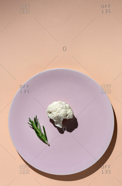 Raw cauliflower bouquet with rosemary from above with sunlight. Flat lay. Top view