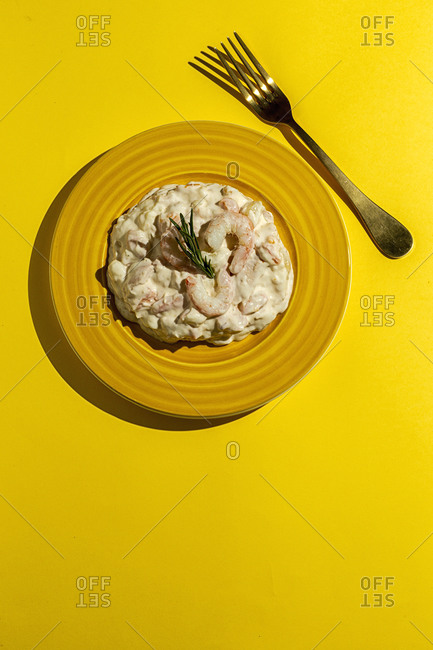 Traditional Russian homemade salad with potatoes, mayonnaise sauce, prawns, carrots, tuna. From above. Flat ay. Top view
