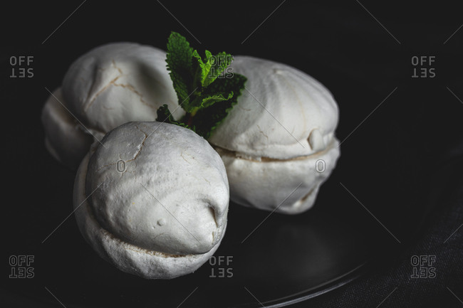 From above homemade white Zefir or Zephyr, Russian traditional dessert with mint on black background