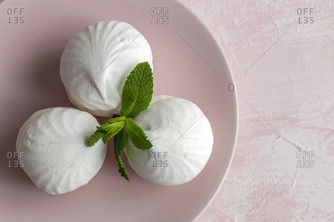 From above top view of homemade white Zefir traditional russian dessert with mint on pink background