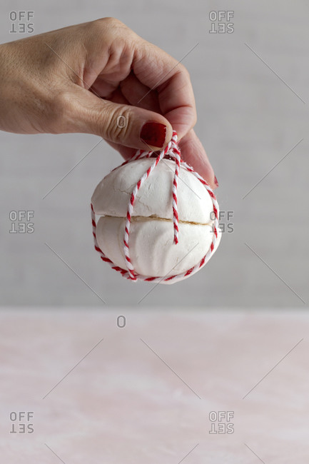 Cropped unrecognizable person holding a homemade white Zefir traditional russian dessert wrapped with rope on pink background
