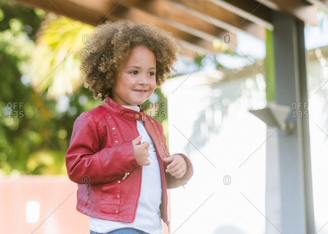 Adorable little girl with curly hair wearing casual shirt smiling looking away while standing on the street