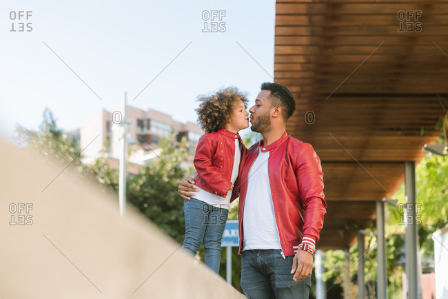 Happy young ethnic man and cute little curly haired daughter wearing similar leather jackets and jeans hugging and kissing while standing together on city street