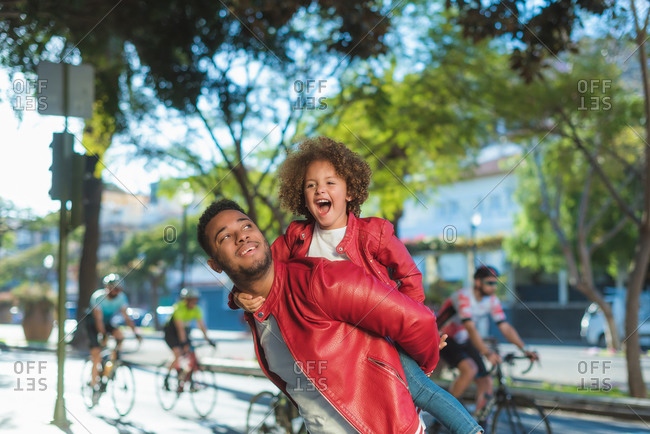 Happy young ethnic man giving piggyback ride to delighted little daughter while enjoying free time together on city street