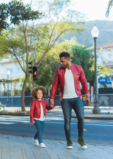Happy young ethnic man with little daughter dressed in similar outfit holding hands while walking on city street in sunny day