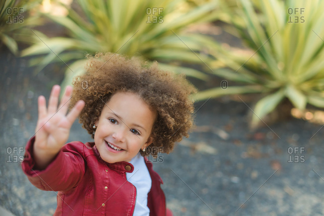 High angle of cheerful little curly haired girl in red jacket showing four fingers and smiling while standing against green tropical plants in park